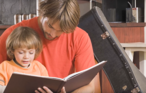 parent reading to child with guitar case in background